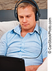 Casual man listening music with headphones at home