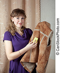 Woman cleaning shammy vest - Woman cleaning shammy vest with...