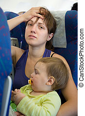 Family in the airplane cabin - women with child in the...