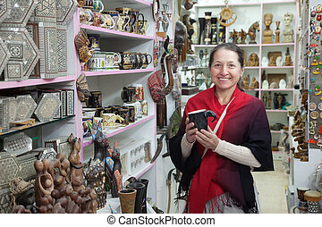 woman chooses souvenirs in egyptian shop - Mature woman...