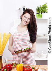 happy smiling young woman in a kitchen adding chopped paprika to her salad in a bowl