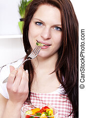young woman in a kitchen eating mixed salad