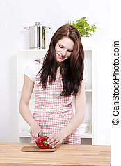 young smiling woman preparing paprika for salad