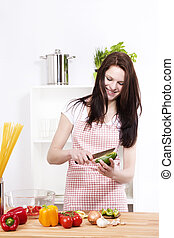 pretty woman in a kitchen chopping green paprika for salad