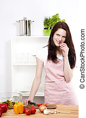 young smiling woman in her kitchen eating tomato