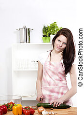 funny woman standing in a kitchen and cutting cucumber
