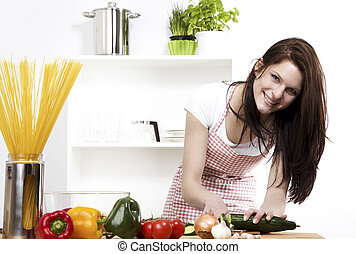 happy woman chopping cucumber for her salad