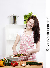 happy woman in kitchen adding cutted cucumber to her salad