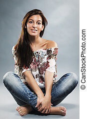 young woman wearing blue jeans sitting on the floor in...