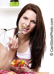 pretty woman in her kitchen eating mixed salad