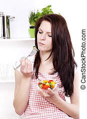 pretty young woman about to eat salad in her kitchen