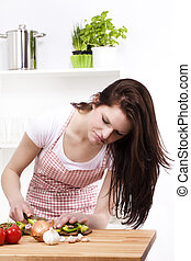 young woman looking at the paprika she is chopping for salad