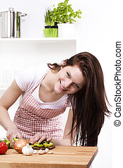 happy young woman in kitchen cutting paprika