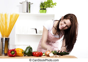 happy woman in kitchen chopping cucumber