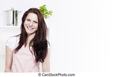 happy smiling young woman in a kitchen