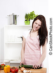 angry woman in a kitchen cutting a cucumber on a chopping...
