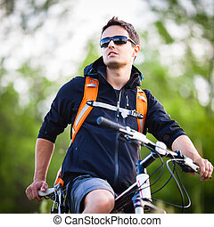 Handsome young man biking in the countryside