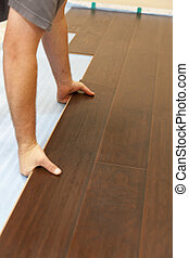 Man Installing New Laminate Wood Flooring Abstract