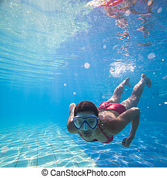 young woman swimming underwater in - Underwater swimming:...
