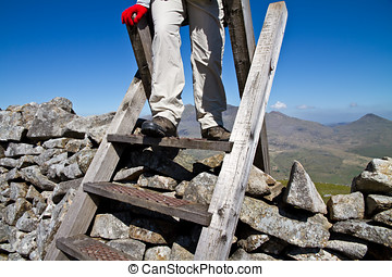 Hillwalking in Wales - Hill walker climbing a ladder over a...