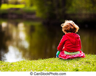 child on the riverside - five year old girl sitting on the...