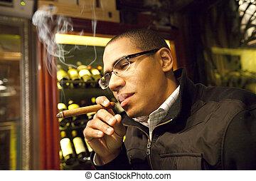 Young Man Smoking A Cigar - Young Hispanic Man Smoking A...