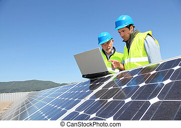 Engineers checking solar panel setup