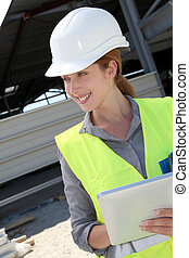 Woman engineer checking building plan on touchpad