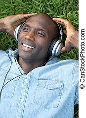 Man laying down in garden with headphones on