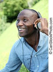 Man relaxing in garden with headphones on