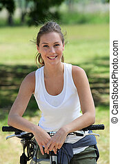 Smiling blonde woman on a bicycle