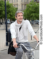 Trendy guy riding bike in town
