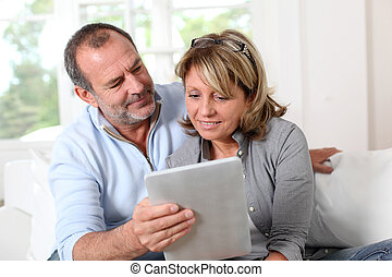 Senior couple looking at web pages on electronic tablet