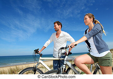 couple, debout, sable, dune, bicycles