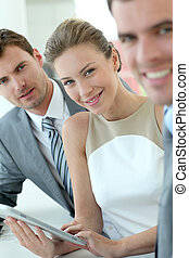 Businesswoman attending meeting with colleagues