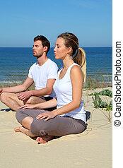 Couple doing yoga exercises on a sandy beach
