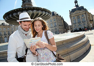 Couple standing by a fountain in Bordeaux with map