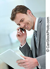 Smiling businessman having a phone call in building hallway