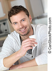 Portrait of handsome guy drinking coffee in home kitchen