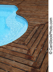 Closeup of swimming pool with wooden floor around