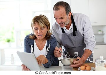 Senior couple having fun in home kitchen