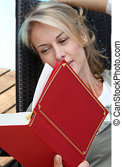 Portrait of woman reading book outside