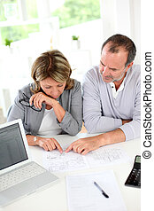 Senior couple reading construction plan in office