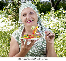 The woman eats salad