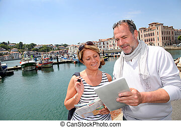 Senior couple using digital tablet to find city tour