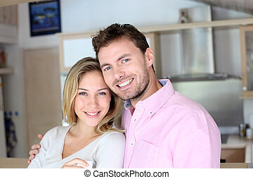 Portrait of in love couple standing in home kitchen