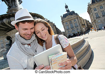 Couple standing by the Place de la Bourse with electronic...