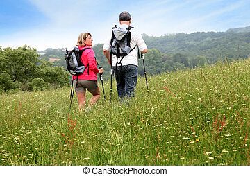 Back view of senior couple hiking in countryside