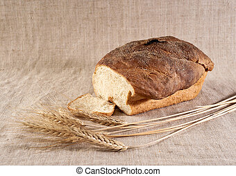 Wheat bread on canvas - Loaf and slice of white wheat bread...