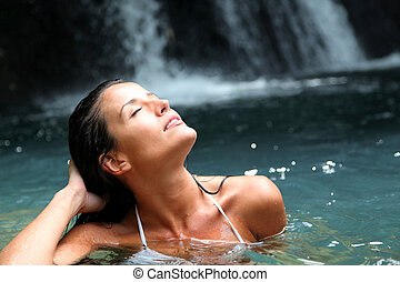 Beautiful woman enjoying bathing near natural waterfall